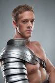Closeup portrait of Gladiator in armour over grey background — Foto Stock