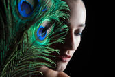 Beautiful brunette young woman with peacock style make-up and pe — Stock Photo