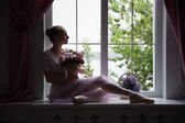 Ballet dancer sitting on windowsill holding flowers — Stock Photo