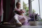 Ballet dancer sitting on windowsill holding flowers — Stock Photo