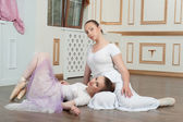 Two beautiful ballet dancers lying on the floor in classical int — Stock Photo