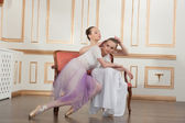 Two young beautiful ballet dancers sitting on sofa in classical — Stock Photo