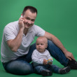 Father and toddler son playing with toy cell phone — Stock Photo #50723475