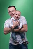 Onun bebek çocuk kucaklayan mutlu gülümseyen baba — Stok fotoğraf