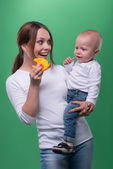 Mother entertaining toddler son with a toy fish — Stock Photo
