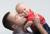 Young handsome father kissing his toddler son — Stock Photo