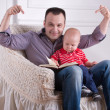 Father and toddler son reading a book — Stock Photo #50850079