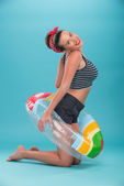 Beautiful girl with pretty smile in pinup style lying on inflata — Stock Photo