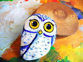 Painted stone owl on a palette — Stok fotoğraf