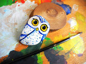 Painted stone owl on a palette — Stock Photo