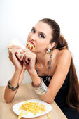 Beautiful glamour woman is eating fast food  — Stock Photo