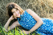Cute teen girl in blue dress sitting on the farm  — Stock Photo