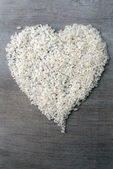 Rice grains formed in heart shape on wooden background  — Zdjęcie stockowe