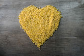Millet grains formed in heart shape on wooden background  — Photo