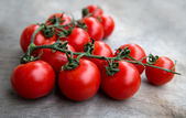 Fresh red delicious tomatoes  on an old wooden tabletop backgrou — Stock Photo