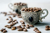 Coffee beans in silver vintage cups on wooden background — Stock Photo