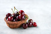 Fresh cherry berries in basket on wooden background — Stock Photo