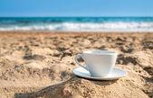 Weiße tasse mit tee oder kaffee auf sand strand meer — Stockfoto