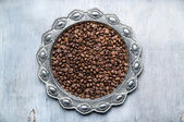 Coffee beans in silver vintage plate on wooden background — Stock Photo
