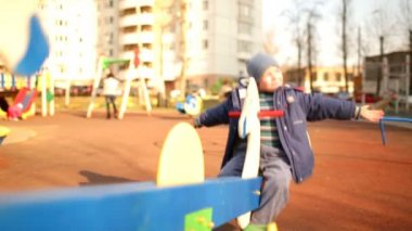 Cheerful boy in a blue dress on a swing. — Stock Video