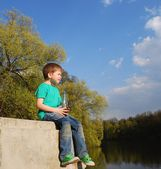 Boy sitting near the water — Stock Photo