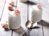 Rose flavor Greek yogurt in a glass jarwith lace — Stock Photo