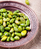 Pistachio nuts in a cooper authentic plate — Stock Photo