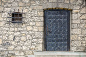 Stone wall texture and ancient door and small window — Stock Photo