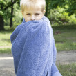 Little cute blond boy five years old wrap up in towel standing on bank of river — Stock Photo #45374341