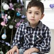 Pensive boy sitting near Christmas tree — Stock Photo #45375689