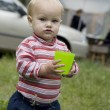 Adorable baby girl playing with plastic cap in the park — Stock Photo #45377387