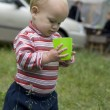 Adorable baby girl playing with plastic cap in the park — Stock Photo #45378751