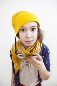 Silly little girl ten years old in yellow knitting  hat — Stock Photo