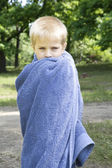 Little cute blond boy five years old wrap up in towel standing on bank of river — Stock Photo