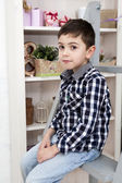 Portrait of a cute little boy sitting on the staircase near chest of drawers — Stock Photo