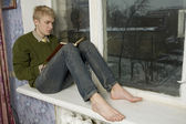 Young handsome man sitting on the window-sill — Stock Photo
