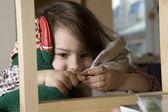 Little cute girl five years okd  looking above bookshelf. — Stock Photo