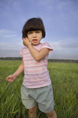 Little girl with grass standing on meadow — Stock Photo