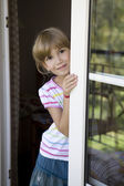 Girl looking out balcony door — Stockfoto