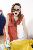 Young furious woman ironing yellow dress — Stock Photo