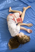 Little dreaming girl lying on the bed — Stock Photo
