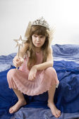 Little upset girl playing in fairy tale — Stock Photo