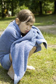 Little cute girl sitting on bank of river — Stock Photo