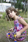 Litle girl sitting on swing — Stock Photo
