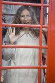 Woman in phone booth — Zdjęcie stockowe