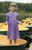 Cute girl standing on boat — Stock Photo