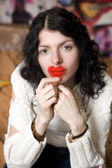 Serious young woman with plastic heart nearby lips — Stock Photo