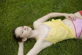 Young woman lying  in summer park — Stock Photo