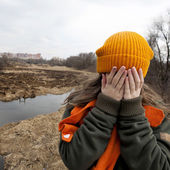 Sad teenager in orange knitten hat — Stockfoto