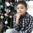 Pensive boy sitting near Christmas tree — Stock Photo #45384885
